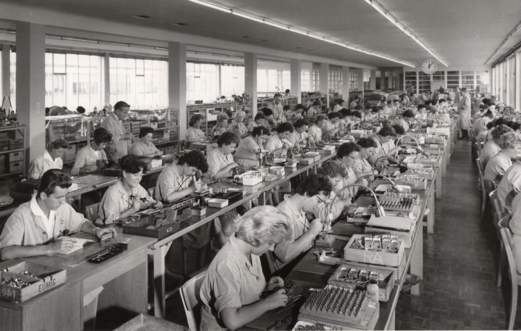 Firmenchronik: Arbeiterinnen in Eumig-Fabrikshalle an Montagetischen